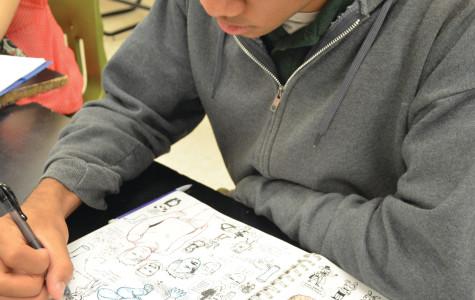 Junior Marcus Jones doodles in his sketchbook at an Illustration Club meeting.