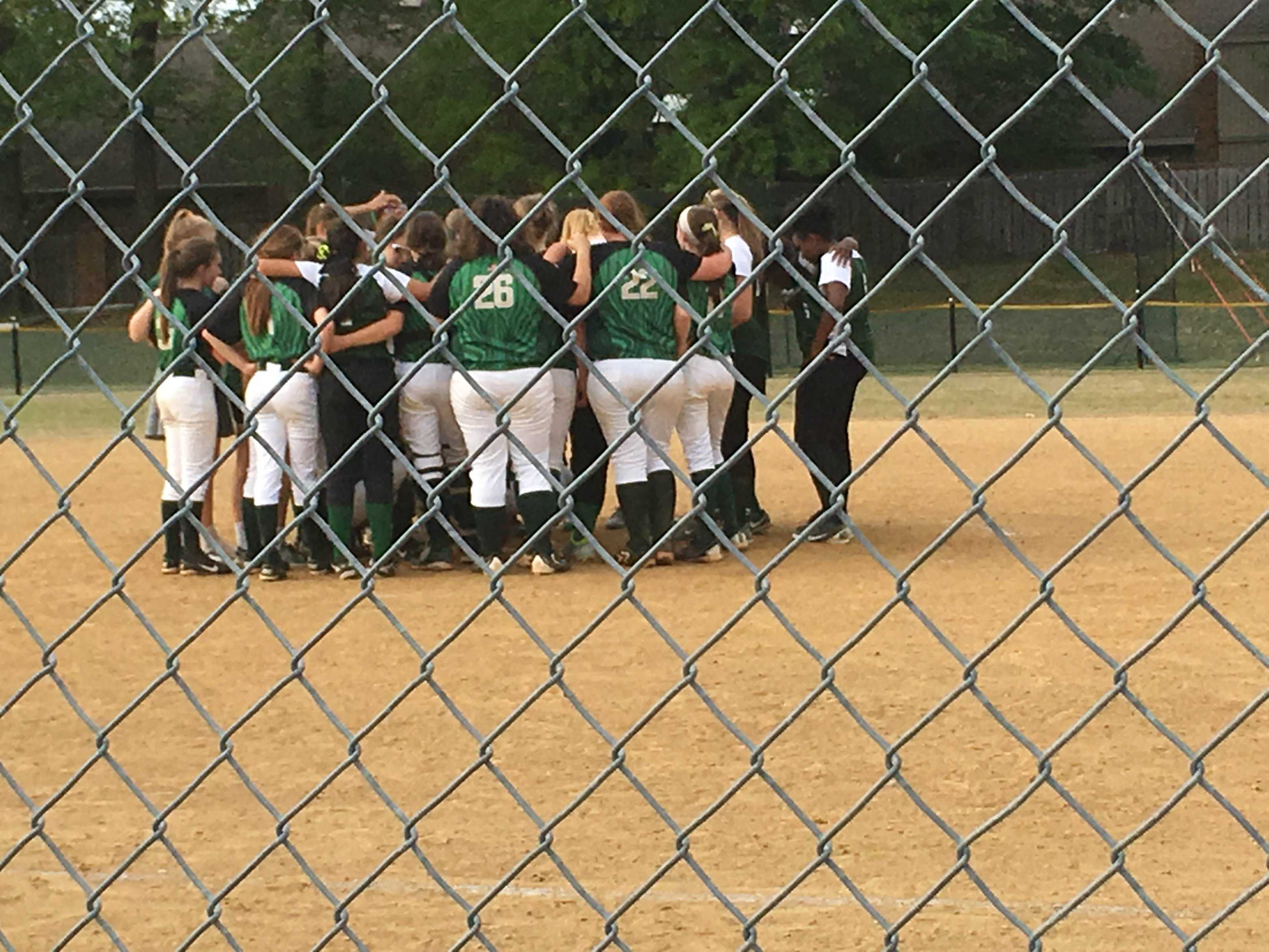 The Lady Spartans and FACS Crusaders in a group huddle after the game on April 18.