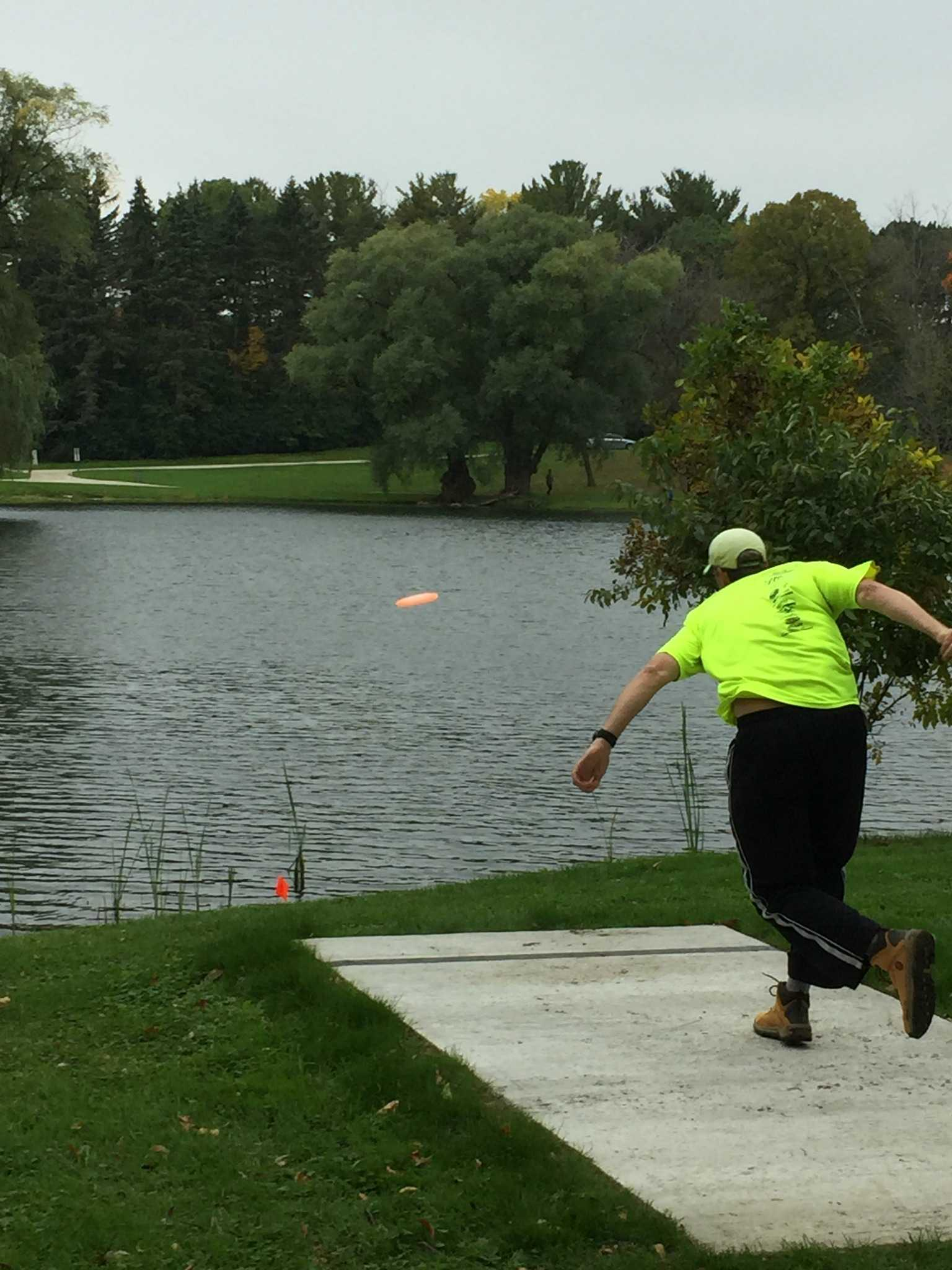 Daniel Zich launches a disc across the lake during his Disc Golf match