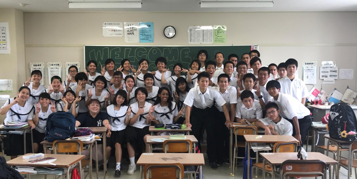 Kaitlin Mottley (11) smiles for a picture with students from Itoman Prefectural
