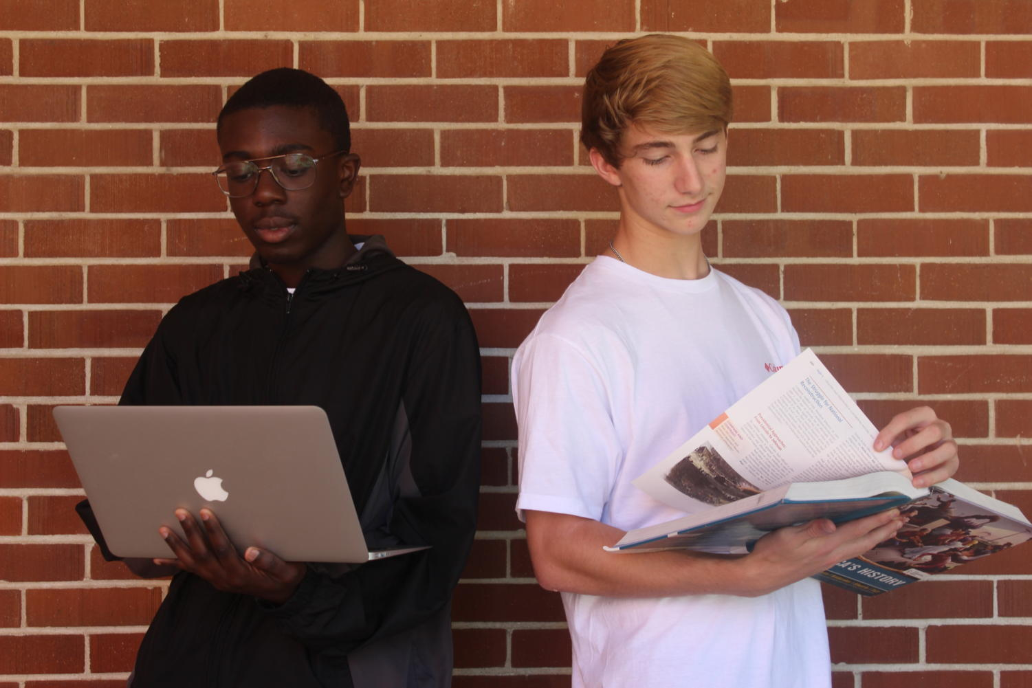 Brandon Mensah (11) studies for his AP US History test using his laptop, while Jacob Hatfield (11) studies with his textbook.