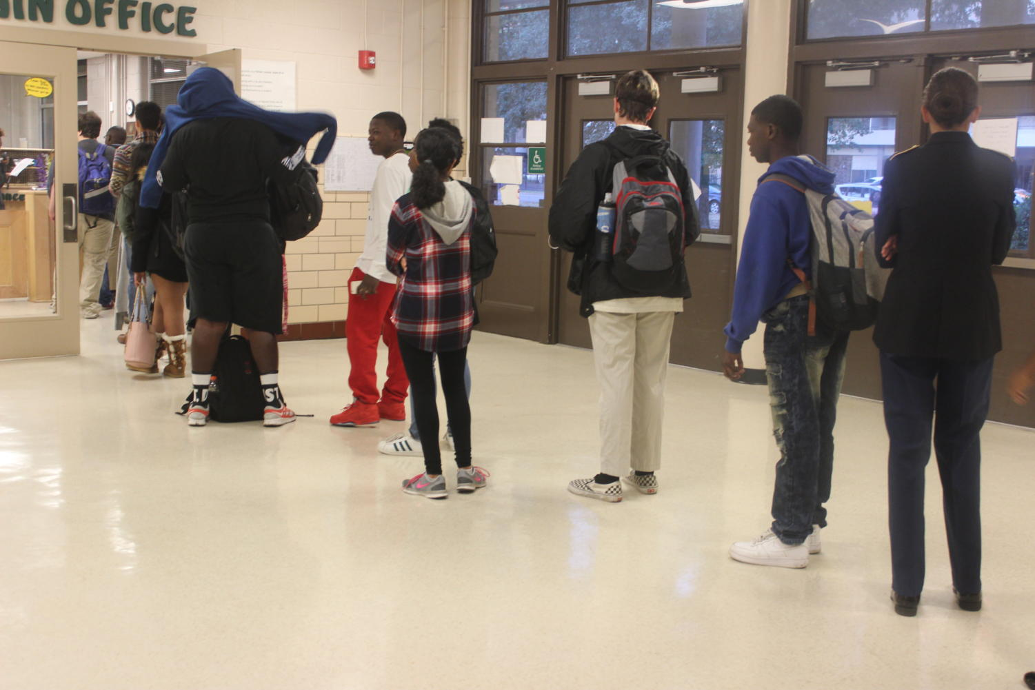 Students line up to collect a tardy slip from the office before school