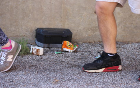 Students walk by trash surrounding one of the many rat traps around the school.