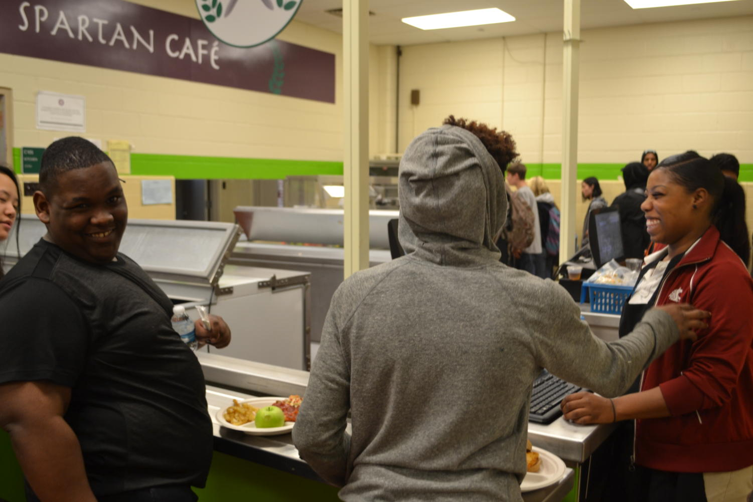Students laugh and chat with cafeteria staff during C lunch.