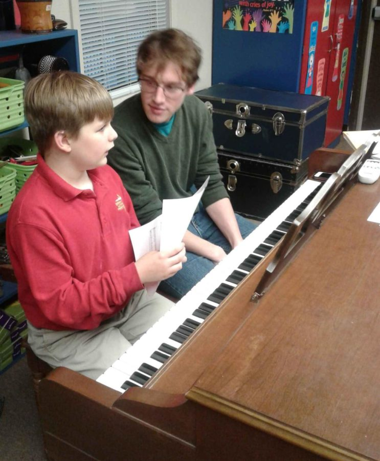 Past student helps a current student in piano lessons at Mr. Jackson's Strive School of Music.
