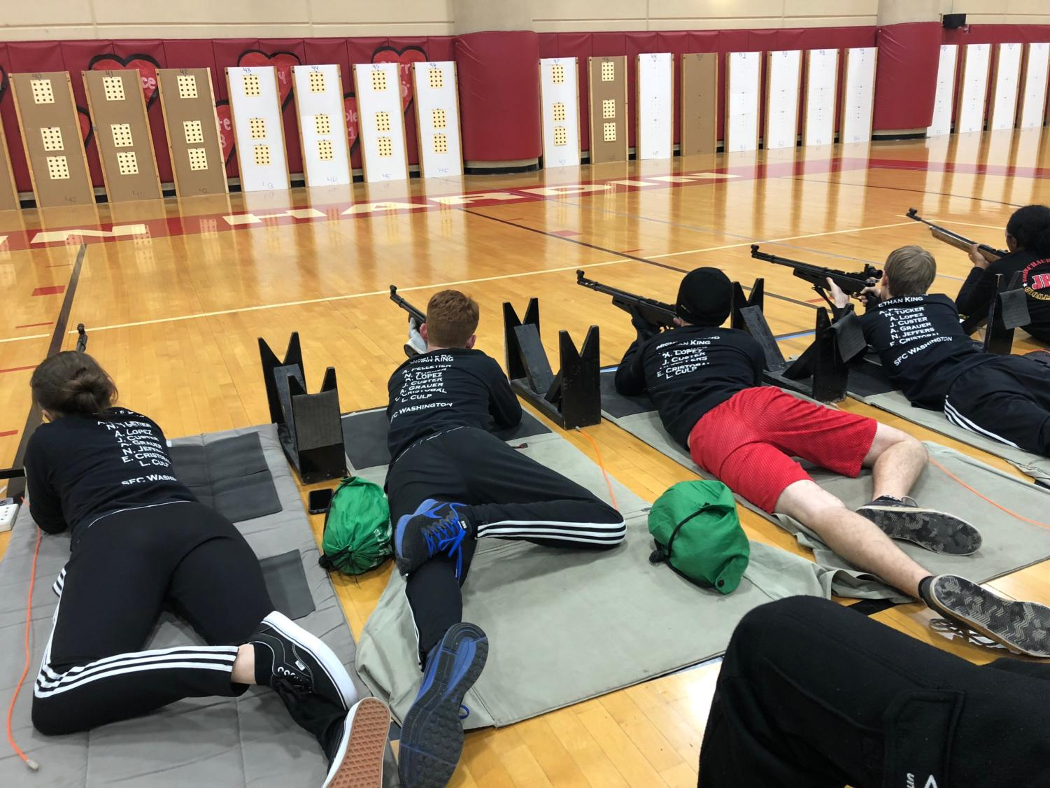 In the prone position, Michelle Bond, Ethan King, and Nathan Tucker compete at the SGM Paul. C Gray JROTC Invitational Marksmanship Competition at John Hardin High School in Fort Knox, Kentucky.