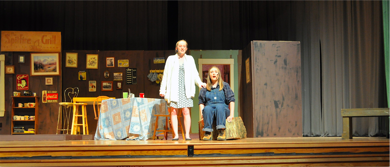Claire Brindley and Rachel Thomas singing onstage during the musical