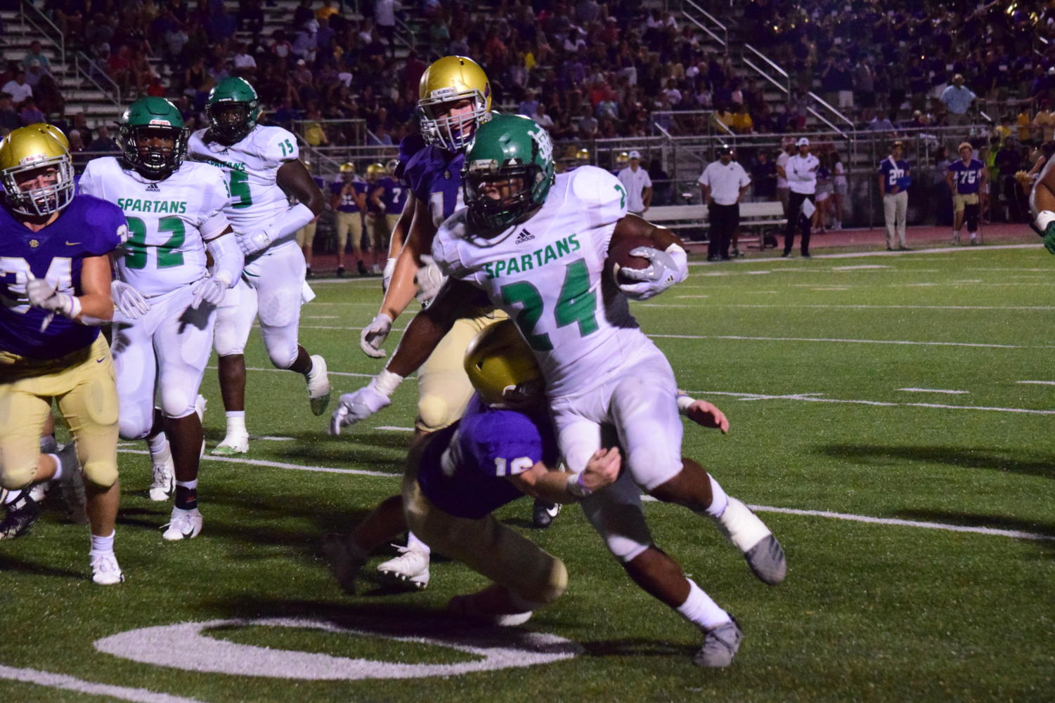 Dodging a tackle, Eli Neal (12) makes a break for the endzone against Christian Brothers.