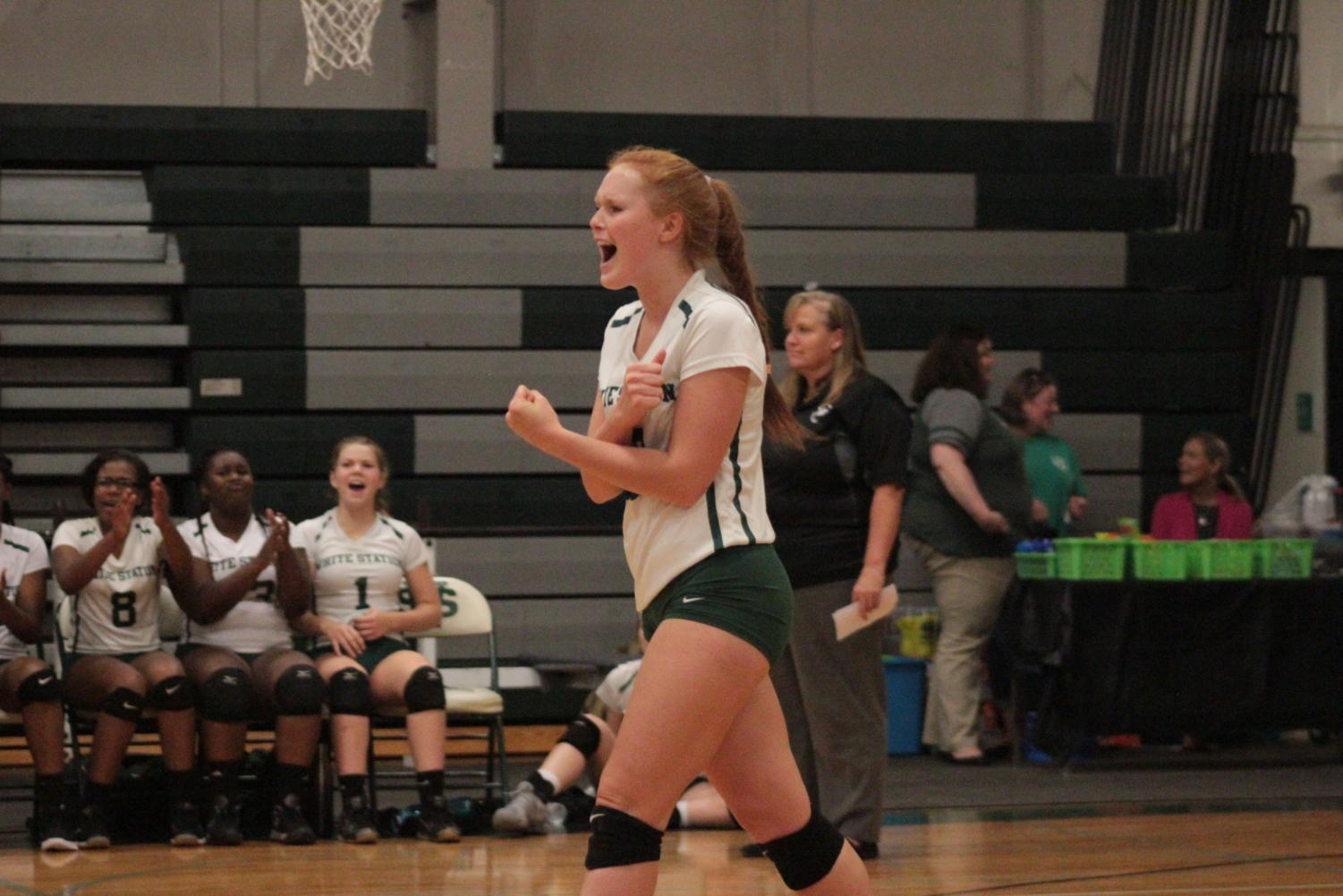To celebrate scoring a point during a tight match, Gigi Ford (12) cheers on her volleyball team who took the fourth set, winning the overall game.