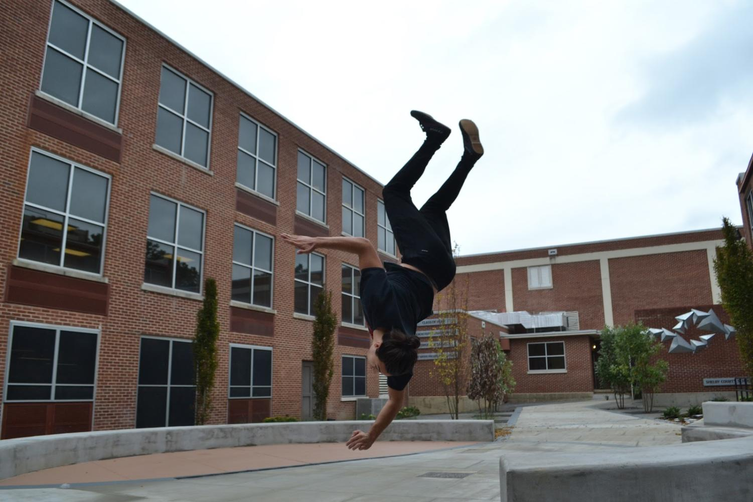 Hayden Gowen (10) completes a front flip in the courtyard at White Station. Gowen began doing parkour in the seventh grade and plans to continue in the future.