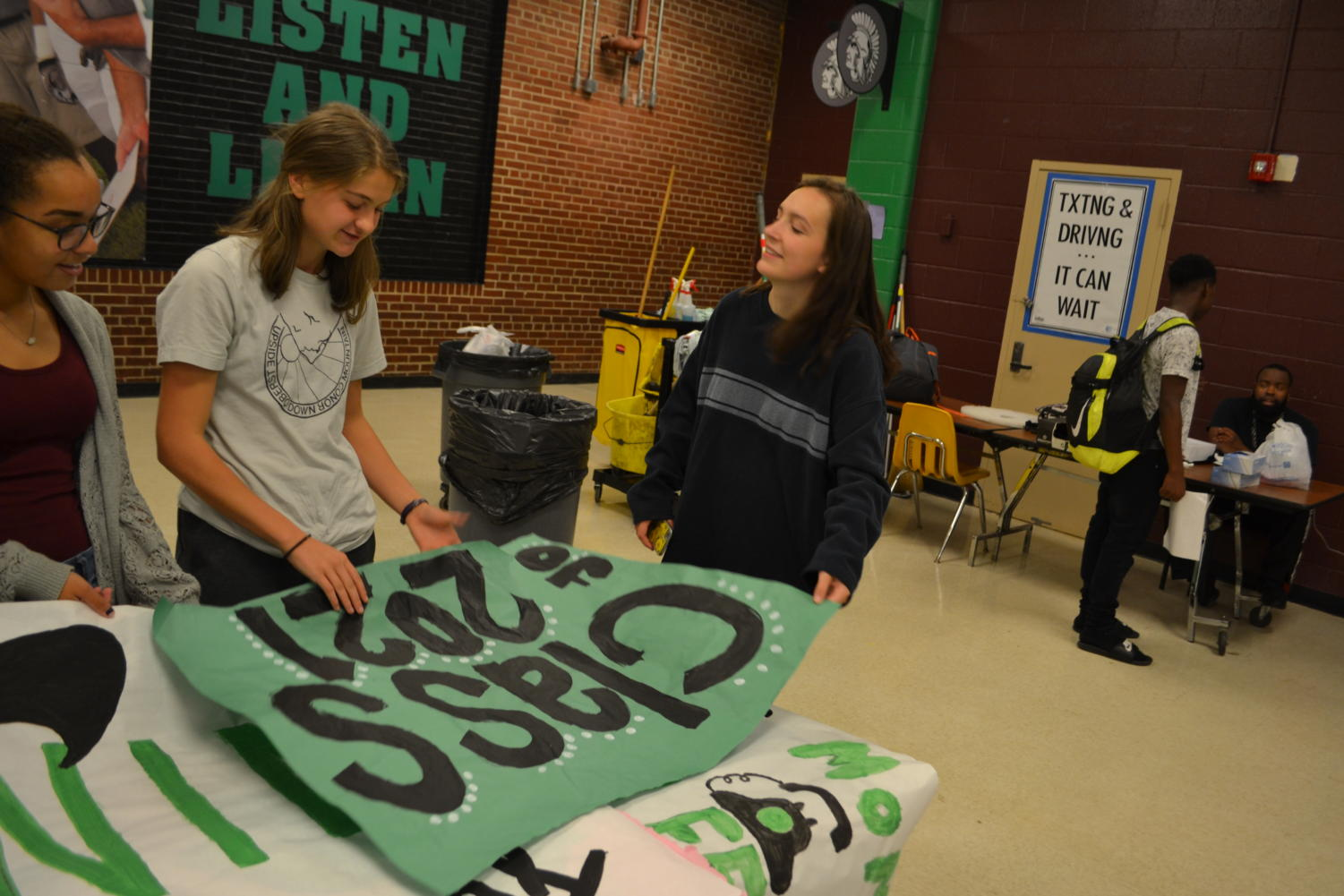 Students (from left) Autumn Jones (10), Amalie Vacanti (10) and Rylie Duke (10) review signs for the Class of 2021.
