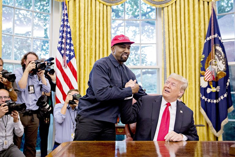 "Known for his political endorsements, Rapper Kanye West greets President Donald Trump during a visit to the Oval Office in October, displaying his support in a ""Make America Great Again"" hat."