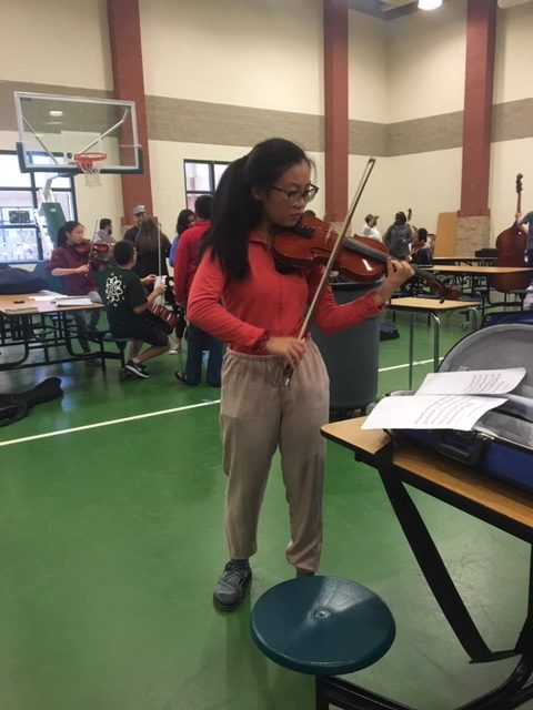 Sophomore Lily Zeng warms up her violin before her audition. Just like an athlete might, musicians must prepare their muscles prior to performances.