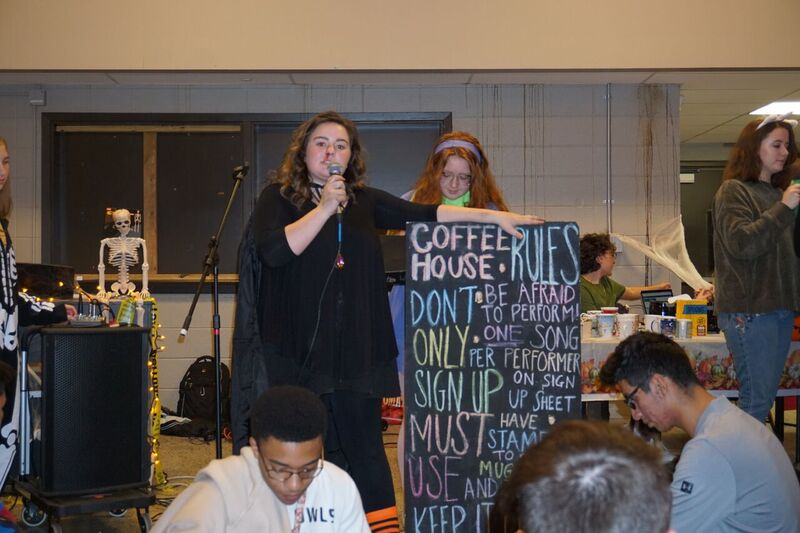 """Senior editor of The Scribbler Savannah Turnage (12) explains the rules and protocol for the October 2018 """"Cereal Killer"""" Coffeehouse to an eager crowd of students."""