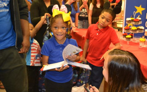 Raegan beams from ear to ear as she receives her autograph book for her trip to Disney World from the Make-A-Wish club.