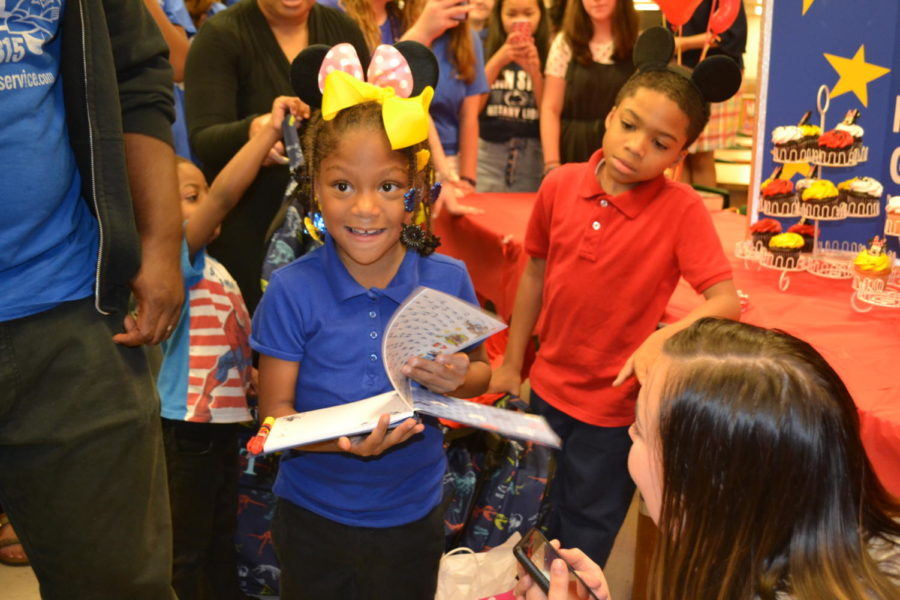 Raegan+beams+from+ear+to+ear+as+she+receives+her+autograph+book+for+her+trip+to+Disney+World+from+the+Make-A-Wish+club.+