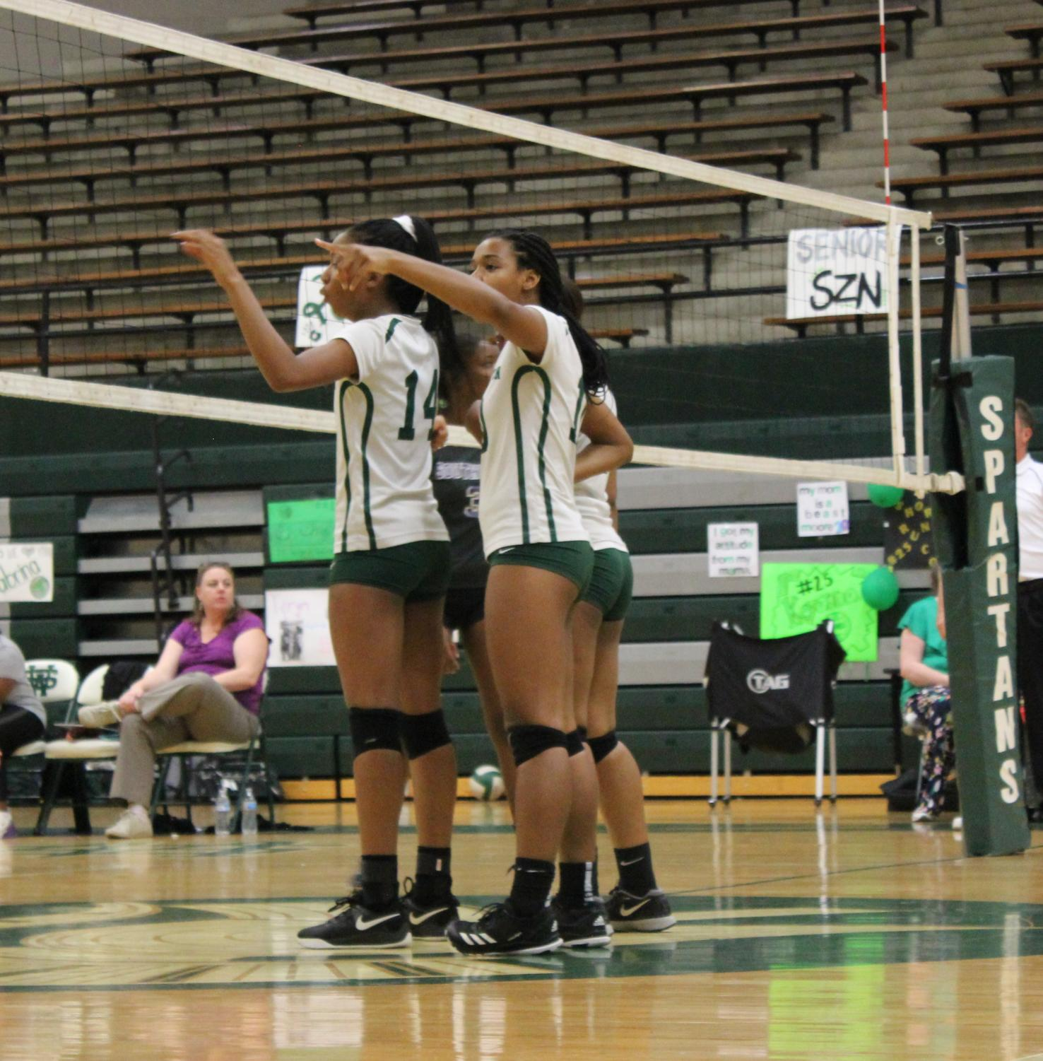 On their senior night, Devyn Davis (12), Taryn Eddie (12), Dayla Rhodes (12), and the rest of the volleyball team prepared for the second set against Southwind. They won the game in three sets.