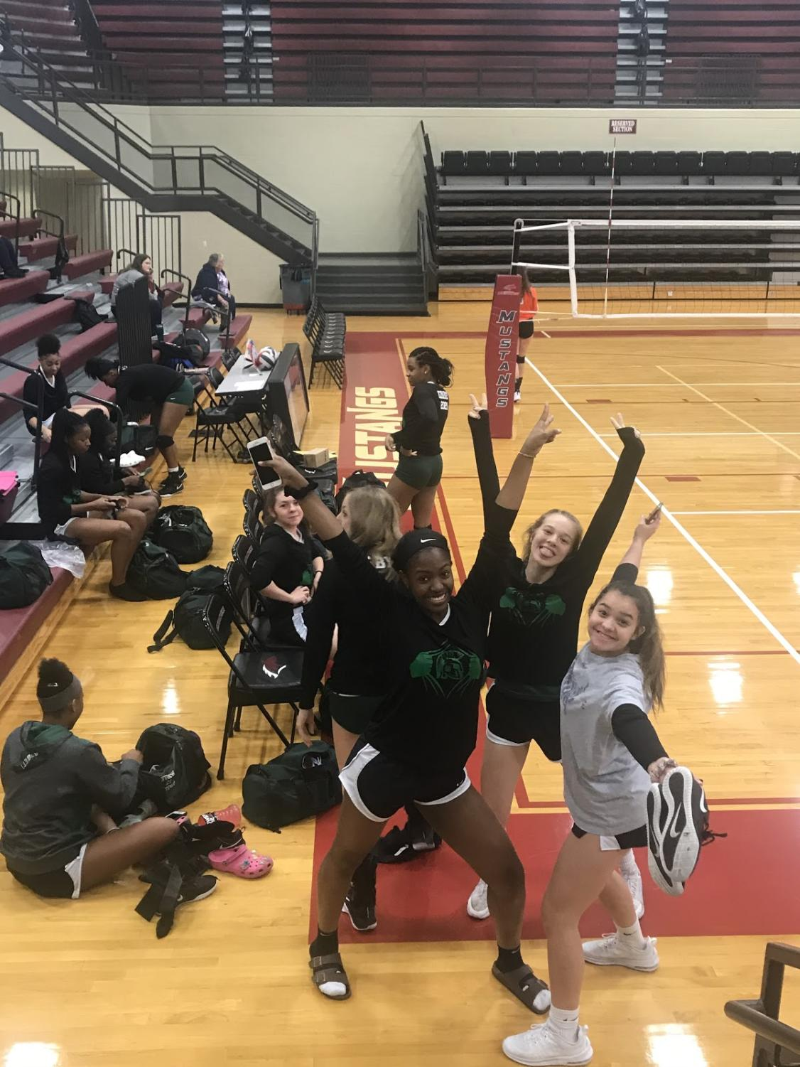 Lauren Roberts (10), McKenzie Cornell (11) and Isabella Garza (10) show their excitement about their first game of the Quad State Tournament in Paducah, Ky. The Lady Spartan volleyball team lost the game against Piggott 2-0.