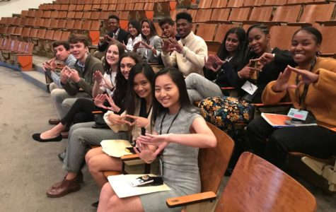 "The current and future members of the DECA Executive Board are seated, waiting for the first presentation of the conference to begin. They are holding up their ""DECA Diamonds"" in support of their chapter."