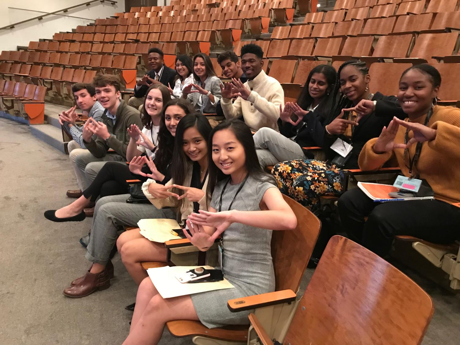 """The current and future members of the DECA Executive Board are seated, waiting for the first presentation of the conference to begin. They are holding up their """"DECA Diamonds"""" in support of their chapter."""
