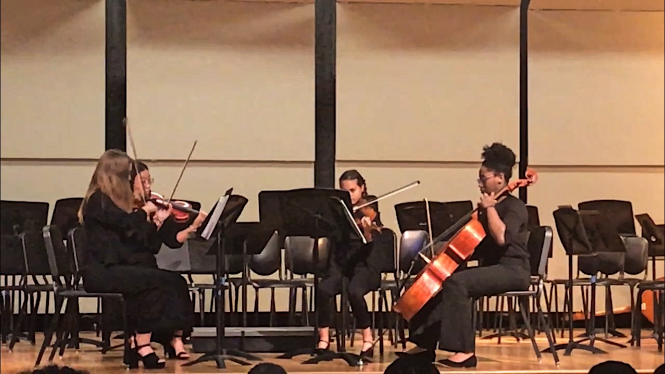 Zoe Wolfe (11), Lily Zeng (11), Abby Cassius (10), and Autumn Bobo (11) take to the stage at the fall orchestra concert and played an arrangement by Shostakovich. Wolfe and Zeng play violin, Cassius plays viola, and Bobo plays cello.