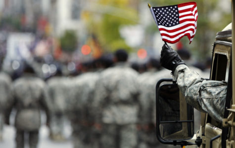 A serviceman waves the American flag during a parade.