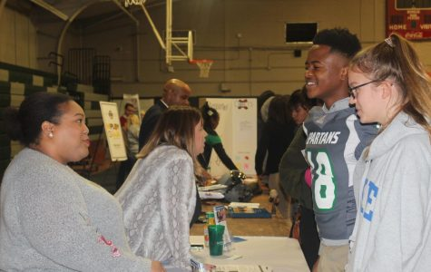 Vance Gieselmann (11) and Antonyio Walker (11) interact with a representative at a half-day career fair. The career fair allowed Spartans to explore their interests.