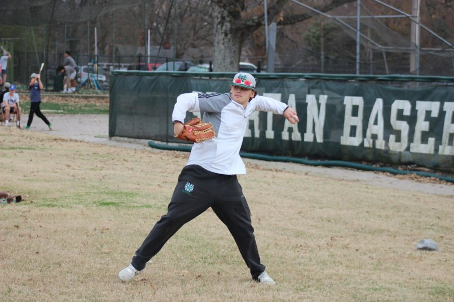 Knox Broach (12) warms up before baseball practice begins. Broach makes his return this season after missing the past 2 seasons due to injury.