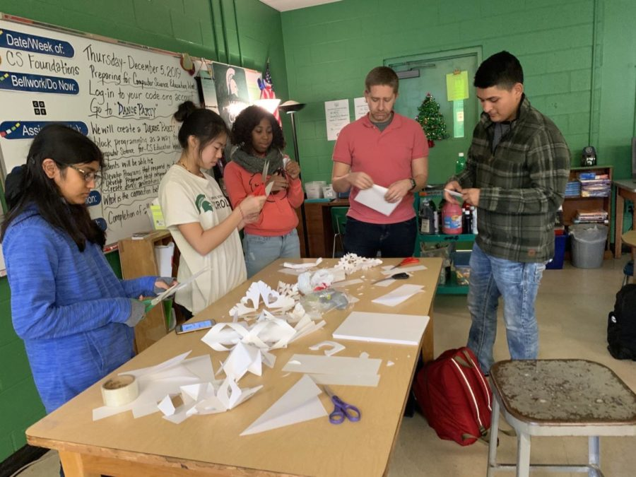 Student council members including teacher Curt Rakestraw create paper snowflakes. This is part of the effort to create winter themed hallways.