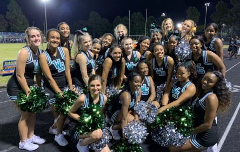 The Spartan Cheer Team poses for a picture after hyping up the crowd at a football game. The team had a successful season, placing second at the MidSouth Regional Cheer Competition.