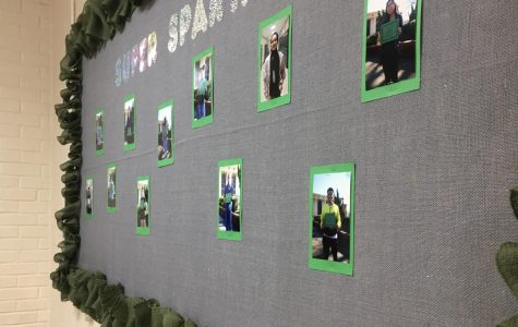 The photos of the Students of the Month are stapled to a green and grey poster, with holographic letters depicting