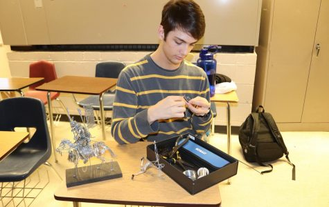 Ben Erickson(12) takes out his equipment in class to work on his latest sculpture. His wire art creations have become recognized by Spartans for their incredible detail and precision.