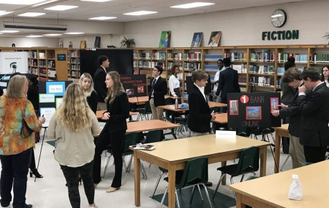 Seniors practice for DECA competition by holding poster session