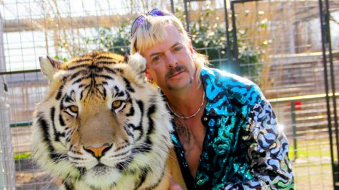 Joe Exotic sporting his signature platinum mullet while getting cozy with a tiger. Netflix