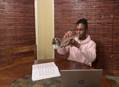 Adam Brooks (12) plays his trumpet, sheet music and laptop at hand. Restrictive virtual policies and snarky trumpet jokes alike haven't stopped students from making music.