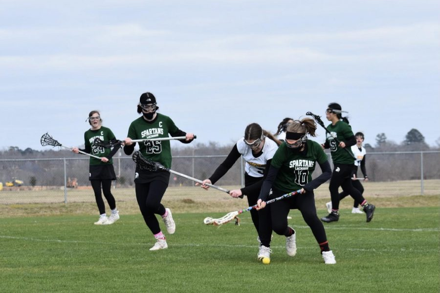 Defender Kendra Sandlin (12) boxes out her opponent as she scoops up a ground ball and begins the transition to offense. The Spartans participated in the LaxFest tournament in Louisiana on February 13 and defeated CE Byrd High School 13-5.