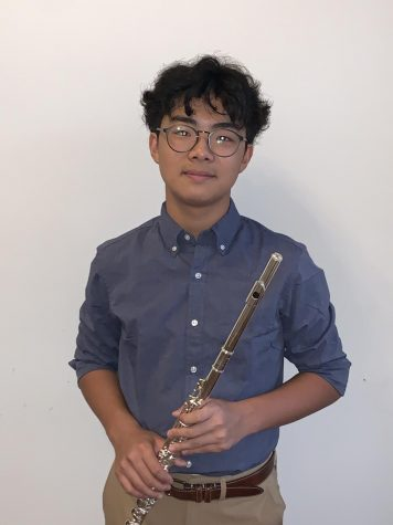 Matthew Kim poses for a headshot with his flute. At the end of last year, Kim received a merit award after seven years of experience.