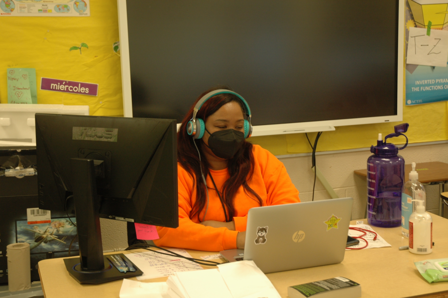 Spanish+teacher+Simone+Gray+incorporates+dual+monitors+to+allow+for+multitasking.+PPE+and+headphones+are+a+must+when+surrounded+by+students+in+the+same+room%2C+but+different+virtual+classes.