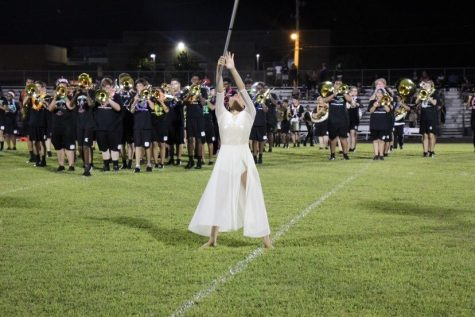 Surrounded by the marching band, Yuan led White Station's color guard team through a 2019 football halftime performance. The color guard team has grown in popularity because of Yuan's leadership and contribution to the sport.