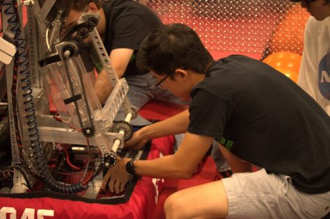 Completing a last minute touch-up before a match, Andrew Chen (12) changes the battery on team 5045's robot. The match was part of an off-season competition known as the First Robotics Challenge in Arkansas.
