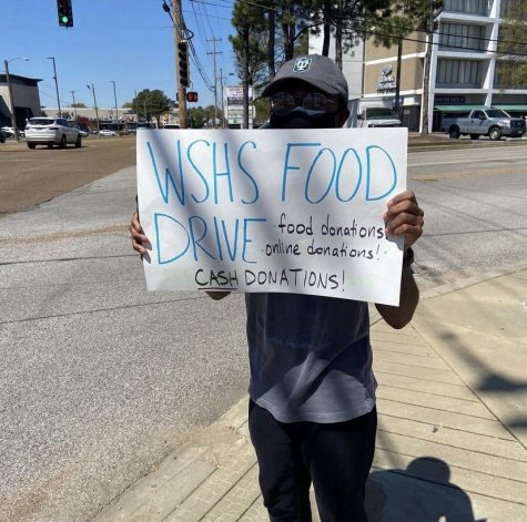 Will Smith (12) stands on a street corner holding up a sign to promote a White Station food drive. As head of the school's service committee, this is just one of many drives he has organized.