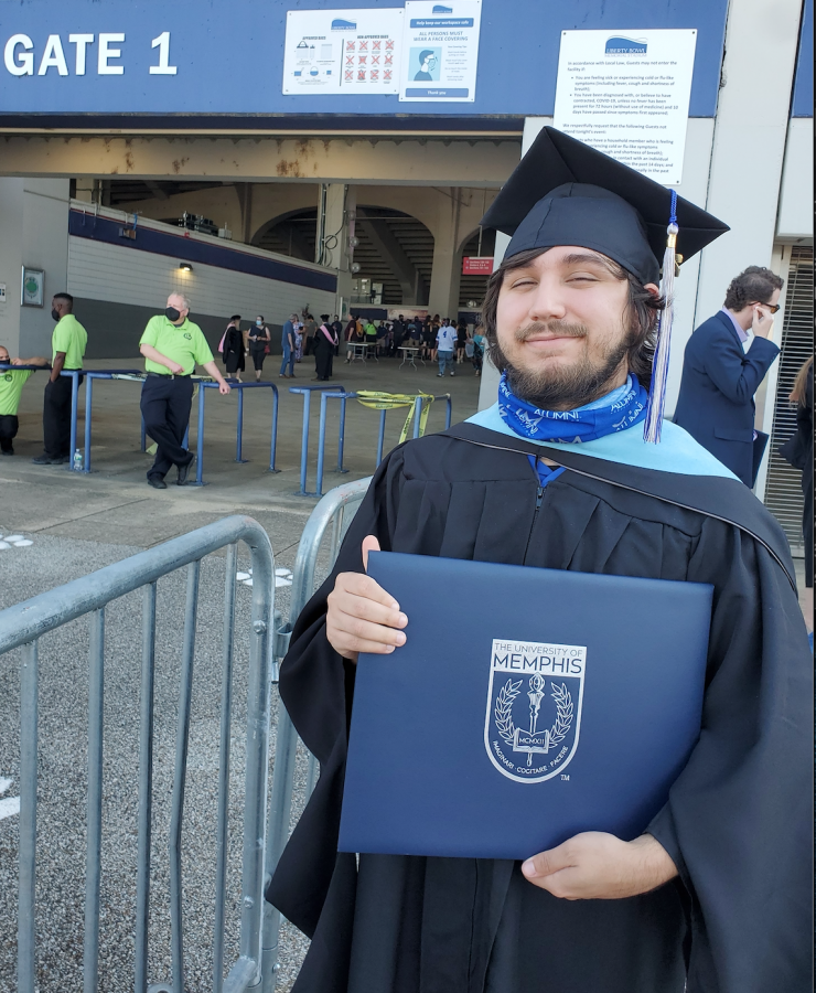 Lira poses with his degree binder at the University of Memphis. He finally finished the requisites needed to graduate from his master's degree this year.