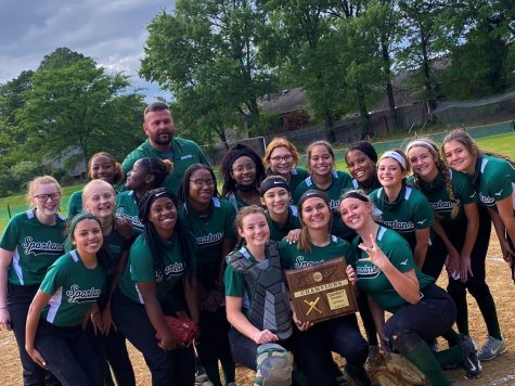 The softball team, led by coach Bob Alberson, poses with their district championship plaque. Despite a unique season with a rushed start, the team managed to conquer tough opponents and overcome the barriers set by COVID-19.