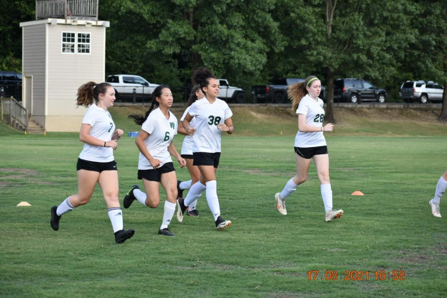 Charged with pent-up energy from last year's nonexistent season, the girls soccer team warms up and prepares to play their first game in a season with only one team instead of the regular two. Seniors experience their last season in a unique way, and underclassmen prepare to play alongside their veteran varsity counterparts.