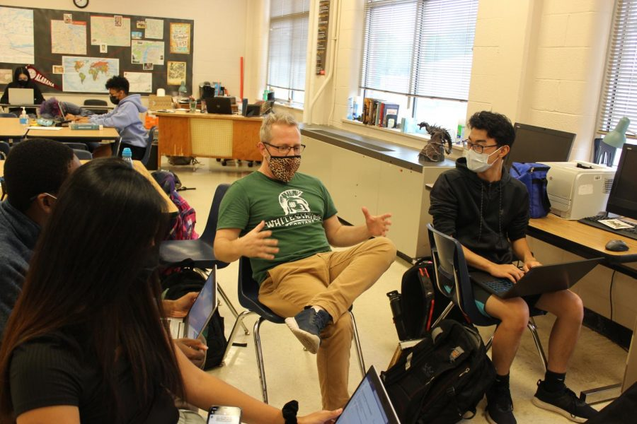 Seth Burgess tells his students a personal anecdote while they work on assignments. Fridays are usually designated as fun workdays for his students when they can work and talk with classmates simultaneously.