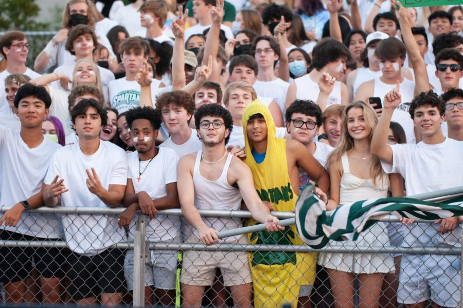 Ben Sharabi (center, fourth from left) waves the flag while Caleb Mohamed (center, fifth from left) sports the 15-year-old banana suit. At Christian Brothers High School, the student section dresses for the white-out theme, preparing for the most popular game of the season.